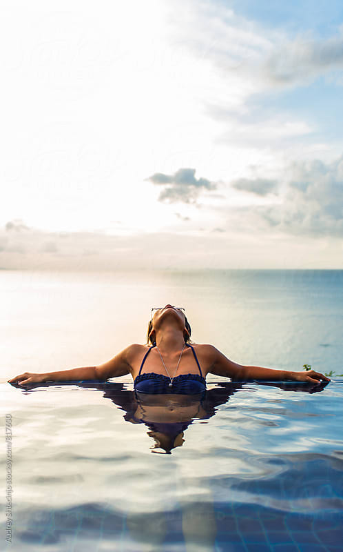 Woman relaxing at the edge of swimming pool with sea horizon and sky in background during sunset. by Marko Milanovic for Stocksy United