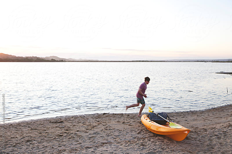 A young boy runs on the beach with a yellow kayak on the sand by Natalie JEFFCOTT for Stocksy United