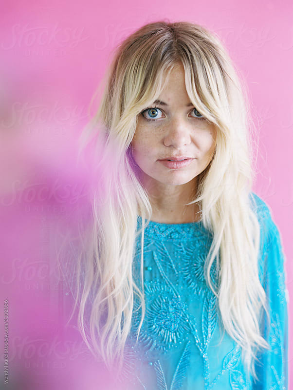 Blonde girl against pink in blue dress by wendy laurel for Stocksy United