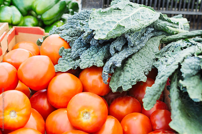 Fresh tomatoes, kale and produce for sale in farmers market stall by Kristin Duvall for Stocksy United