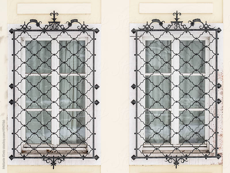 Two windows with baroque lattice screens by Melanie Kintz for Stocksy United