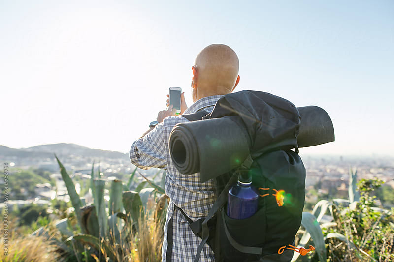 Senior hiker man taking a photo on his phone over the city landscape. by BONNINSTUDIO for Stocksy United