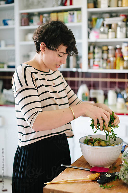 Tossing salad in the kitchen. by Cherish Bryck for Stocksy United