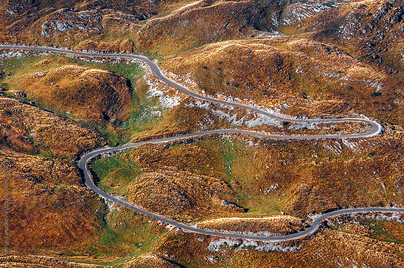 Aerial view of road heading through the mountains by Dimitrije Tanaskovic for Stocksy United