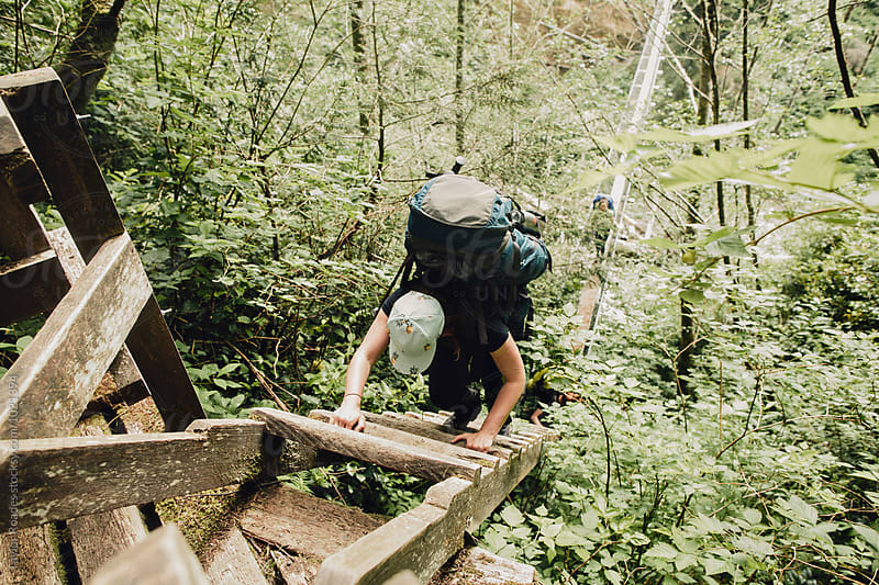 Girl Climbing Ladder while on a hike  by Taylor Roades for Stocksy United