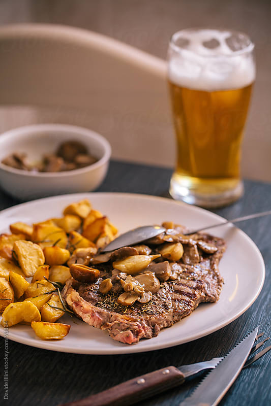 Beef steak with potatoes and mushrooms by Davide Illini for Stocksy United
