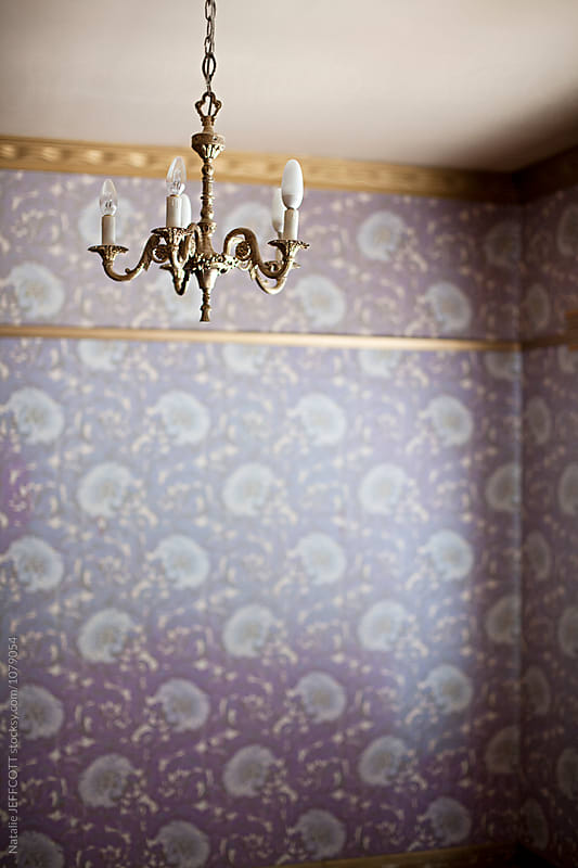 retro chandelier hanging in empty room with purple wallpaper by Natalie JEFFCOTT for Stocksy United