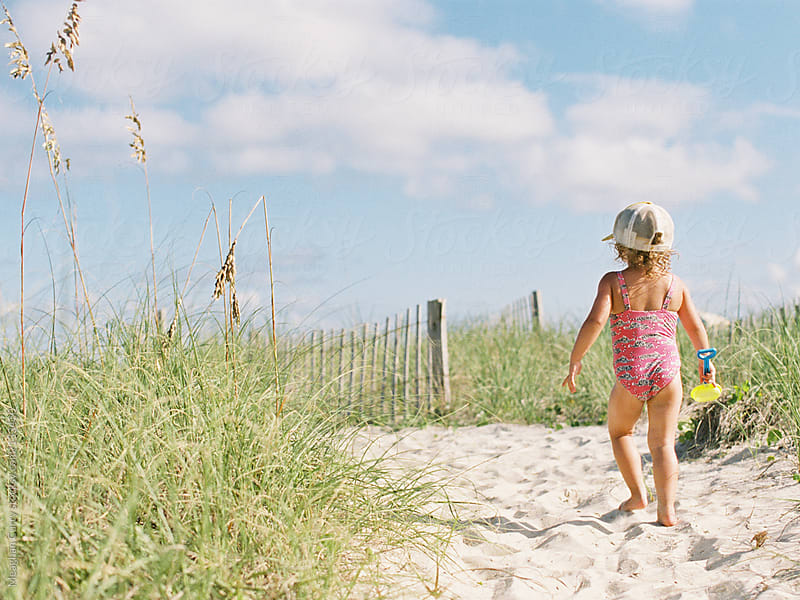 little girl playing at the beach by Meaghan Curry for Stocksy United