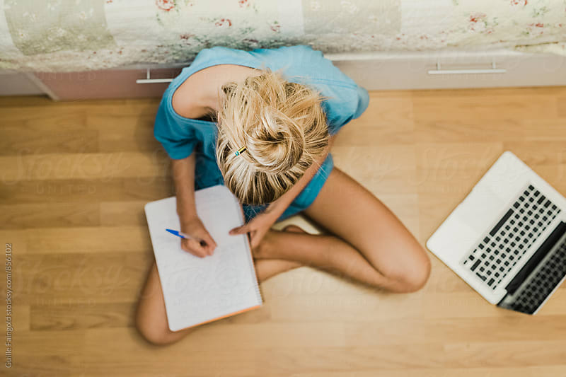 Overhead of blonde woman writing down in notebook by Guille Faingold for Stocksy United