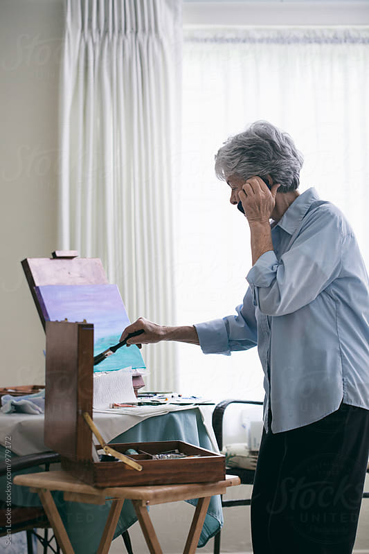Senior: Woman Talking On Cell Phone While Painting Canvas by Sean Locke for Stocksy United