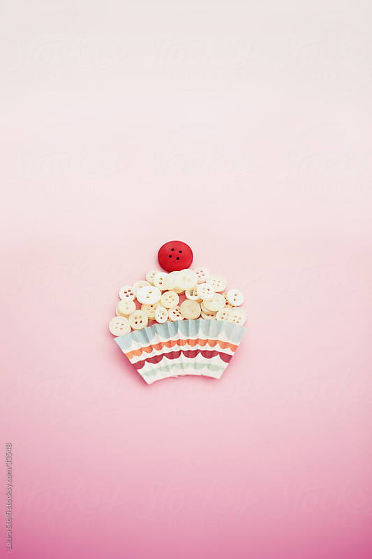 Cupcake made of vintage buttons on pale pink background by Laura Stolfi for Stocksy United