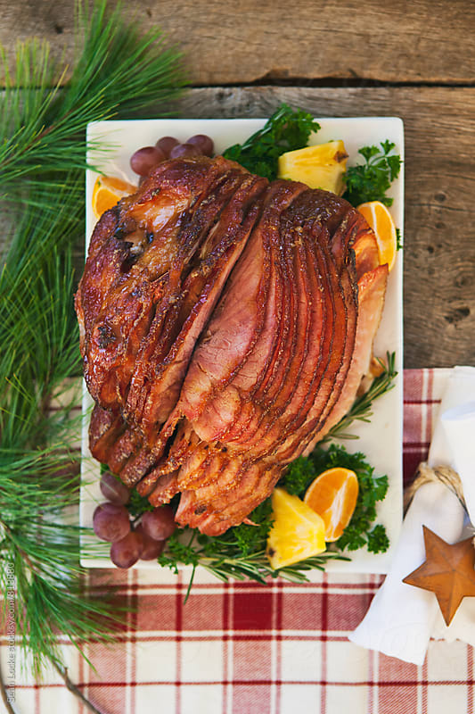 Christmas: Holiday Glazed Ham On Festive Tablecloth by Sean Locke for Stocksy United