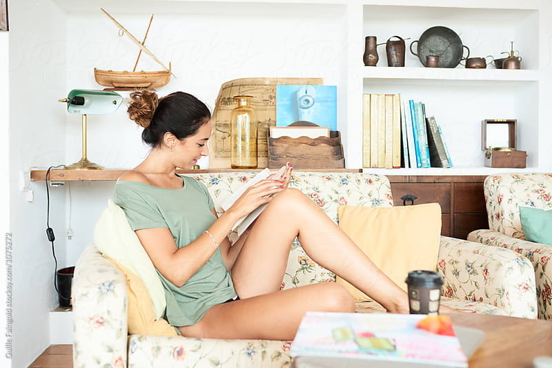 Brunette with tail in bun reading book on sofa by Guille Faingold for Stocksy United