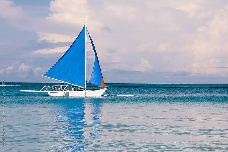 Blue sailboat on turquoise sea by Alejandro Moreno de Carlos for Stocksy United