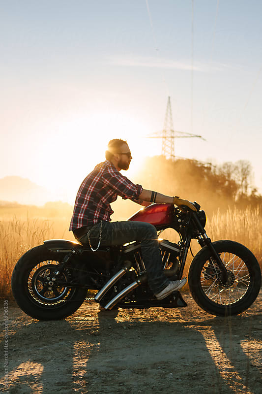 wild, young and free - casual bearded guy sitting on his bike on a dirty road at sunset by Leander Nardin for Stocksy United