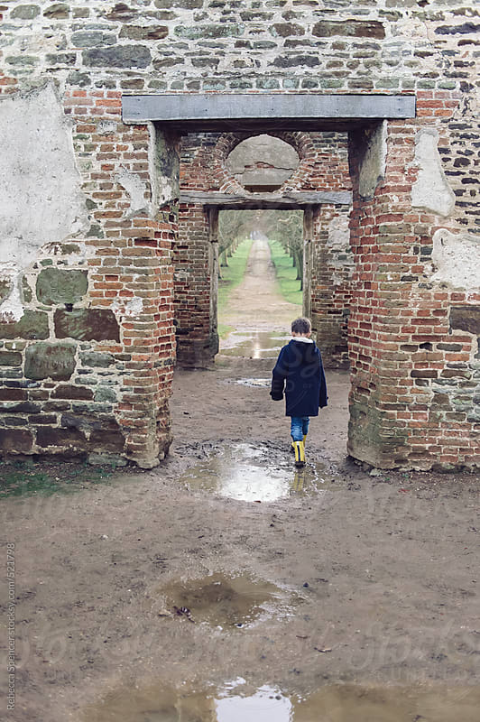 Child walking through ruined old building by Rebecca Spencer for Stocksy United