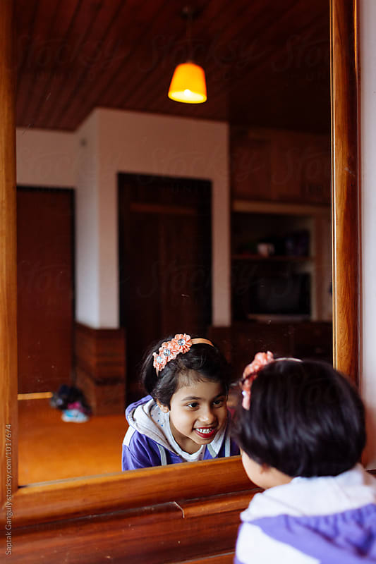 Little girl looking at her lips in the mirror by Saptak Ganguly for Stocksy United