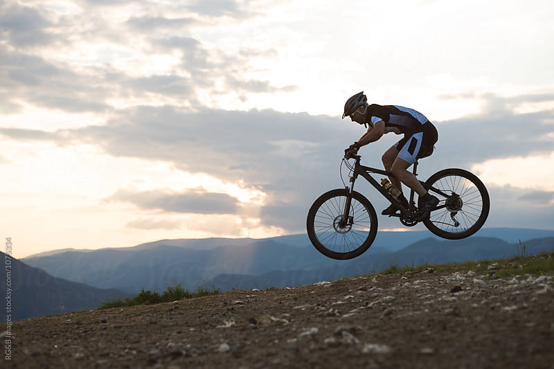 Man jumping on mountain bike with sunset in the background by RG&B Images for Stocksy United