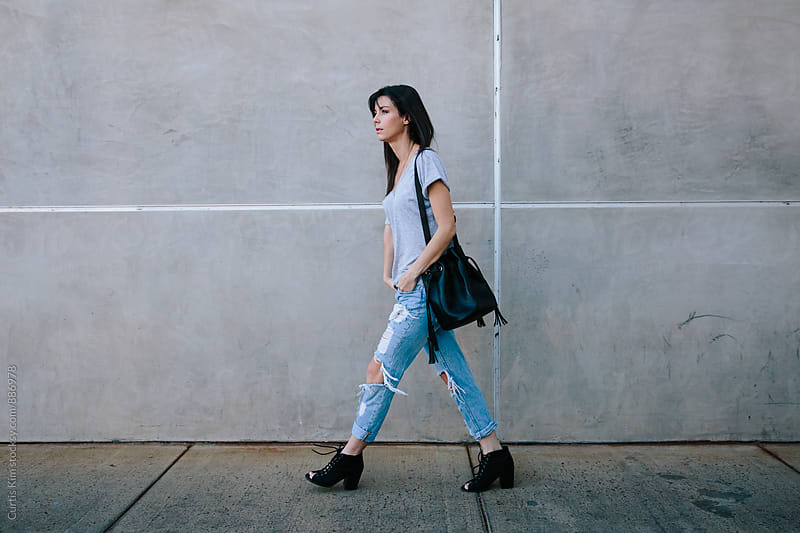 Trendy young woman walking with purse by Curtis Kim for Stocksy United