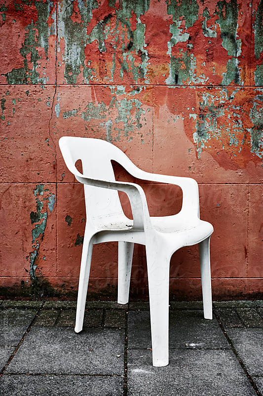 A white plastic chair on the pavement by James Ross for Stocksy United