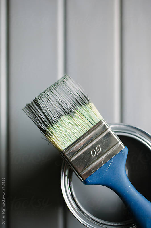 Paint brush and open tin of paint on a grey background. by Darren Muir for Stocksy United