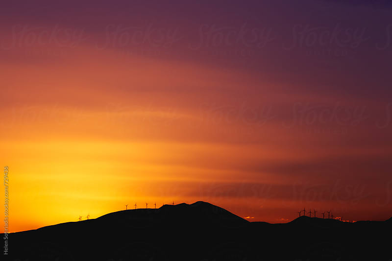 Mountain Ridge with Windmills over a Dark Red Sunset by Helen Sotiriadis for Stocksy United