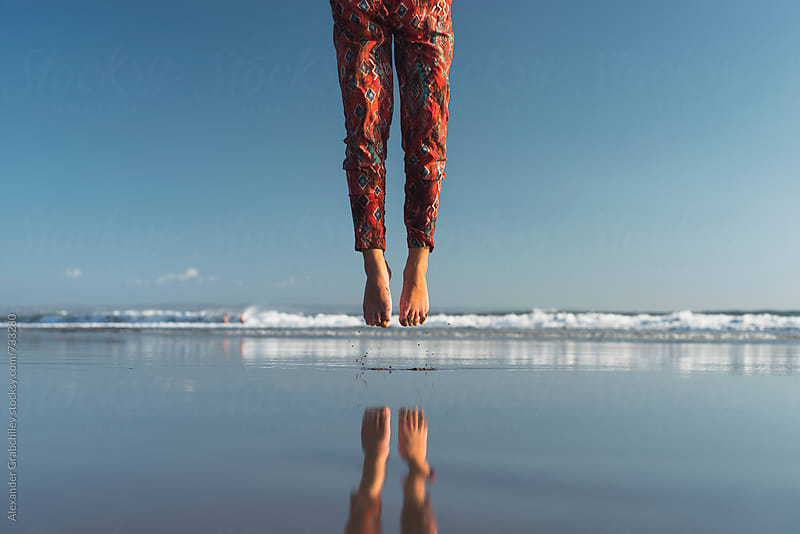 Woman Jumping At Ocean Beach by Alexander Grabchilev for Stocksy United