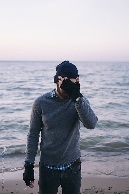 Bearded man standing near the sea, covering his face with hand by Danil Nevsky for Stocksy United