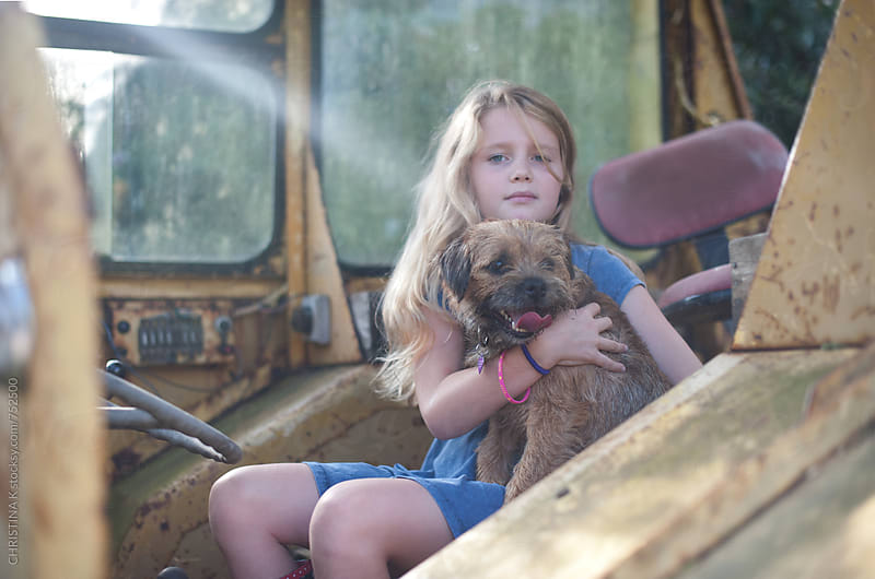 Girl and her dog in a tractor by Christina Kilgour for Stocksy United