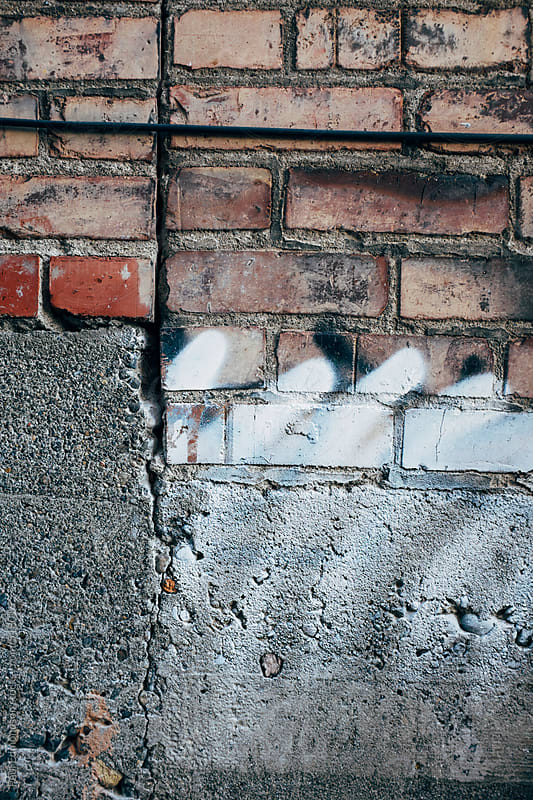 Graffiti paint on brick wall, close up by Paul Edmondson for Stocksy United