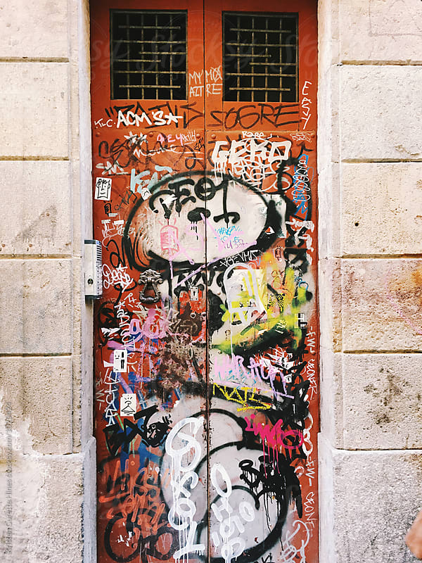 Mobile phone capture of a grafitti door in an alleyway by Kristen Curette Hines for Stocksy United