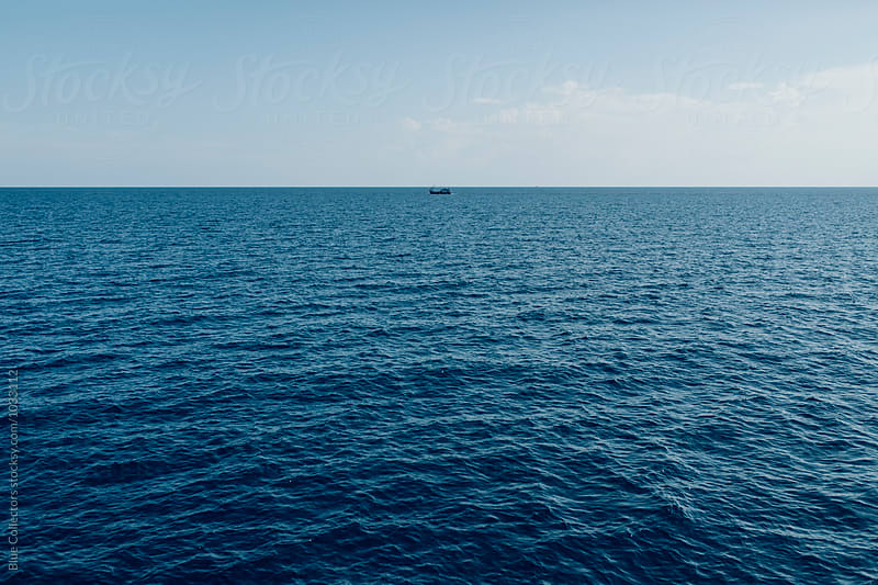 small boat sailing the deep blue sea by Jordi Rulló for Stocksy United