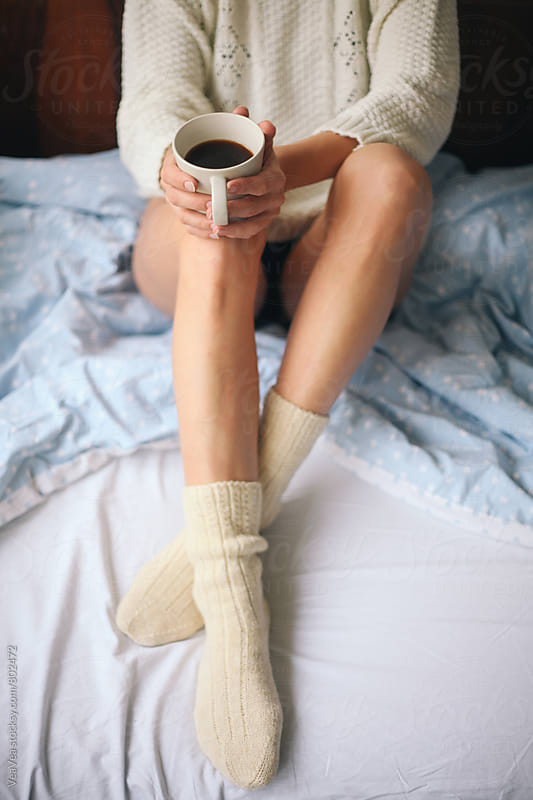 Woman holding cup of coffee sitting on the bed by Marija Mandic for Stocksy United