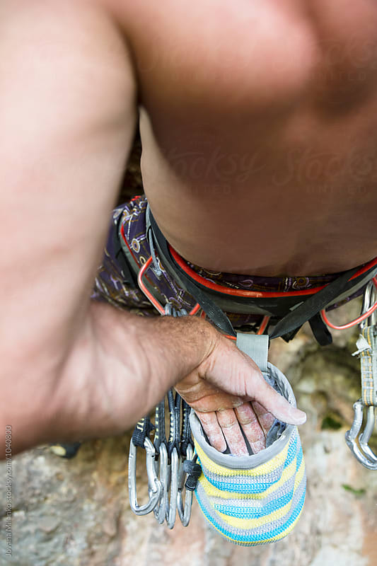 Free climber putting his hand in chalk bag while climbing a route on a natural rock outdoor by Jovana Milanko for Stocksy United
