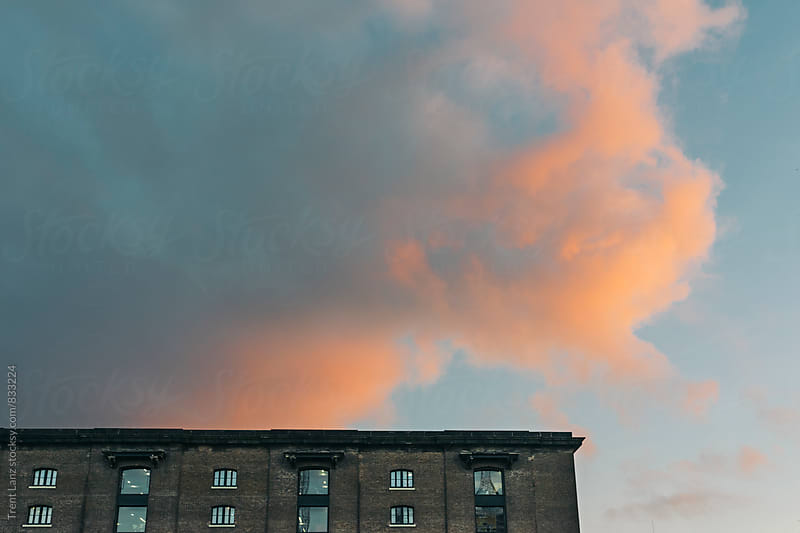 Architectural Building with fluffy clouds colored in blue, orange and pink by Trent Lanz for Stocksy United