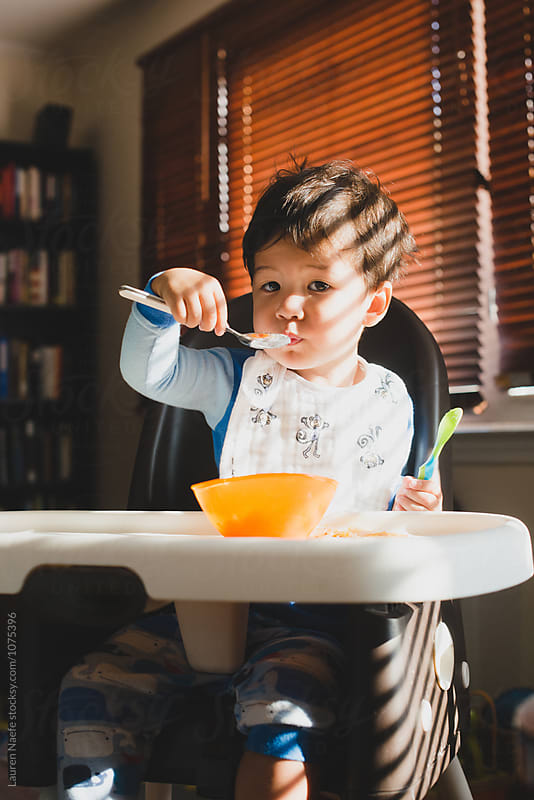 Toddler boy eating breakfast by Lauren Naefe for Stocksy United