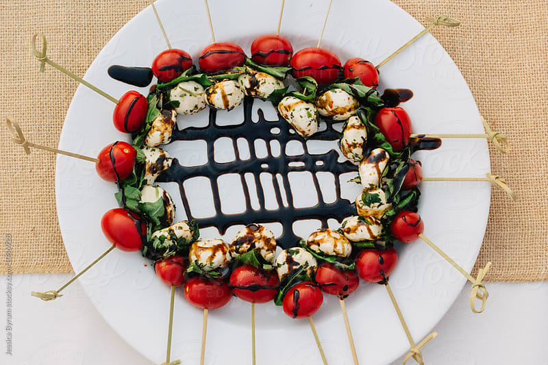 Tomato and mozzarella caprese skewer hors d'oeuvres a plate. by Jessica Byrum for Stocksy United