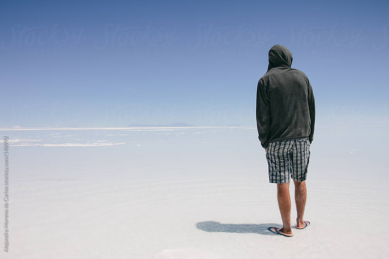 Portrait of young man facing back looking to the infinite with hoodie and sandals in Uyuni by Alejandro Moreno de Carlos for Stocksy United