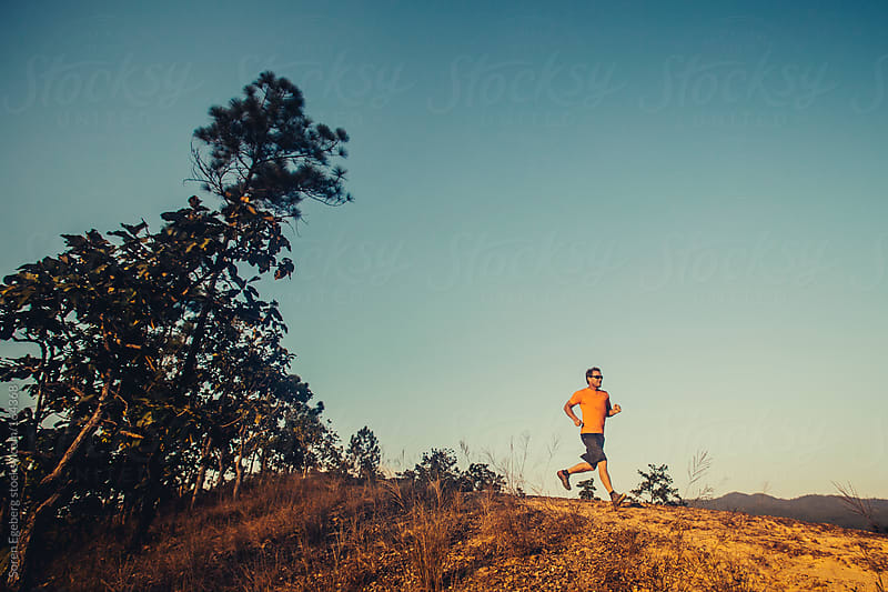 Man trail running outside in nature with trees in warm light by Soren Egeberg for Stocksy United