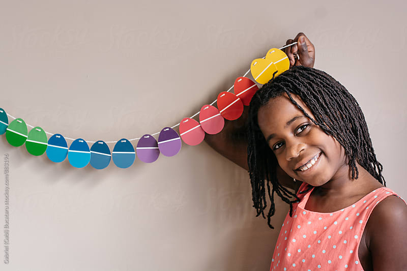 Smiling black girl holding an Easter banner by Gabriel (Gabi) Bucataru for Stocksy United