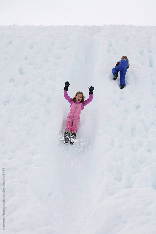 Nine year old girl in pink snowsuit enjoys a ride down a snow chute while little brother climbs up by Carleton Photography for Stocksy United
