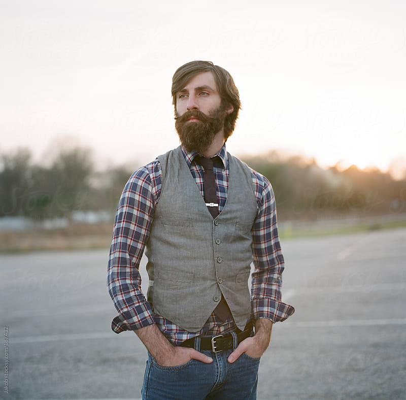 Square portrait of a stylish and bearded man in a parking lot by Jakob for Stocksy United
