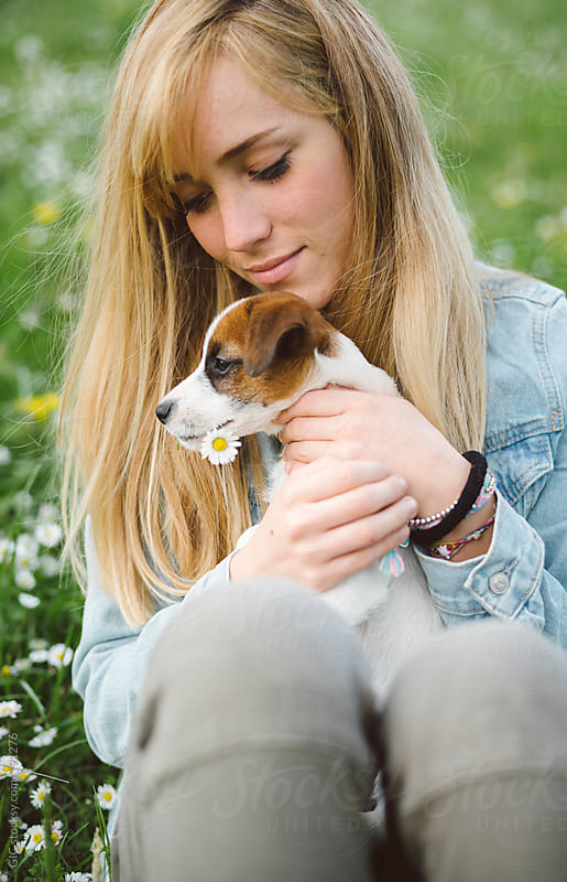 Young woman hugging a Jack Rusell puppy outdoors by GIC for Stocksy United