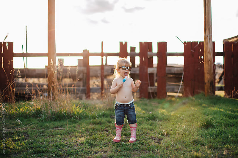 Toddler girl in rubber boots eating popsicle by Jessica Byrum for Stocksy United