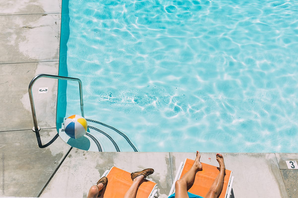 Legs Of Man And Woman Lounging On Orange Lawn Chairs By Swimming Pool By  Luke Mattson
