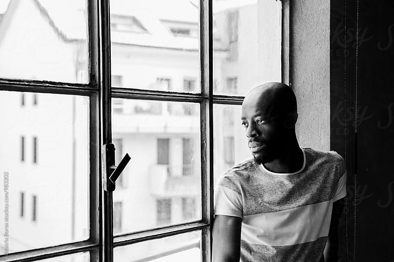 Black and white portrait of a black man looking out of the window by Beatrix Boros for Stocksy United