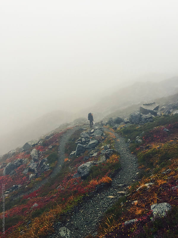 Solo Hiker Climbing Winding Mountain Path Through The Fog by Luke Mattson for Stocksy United