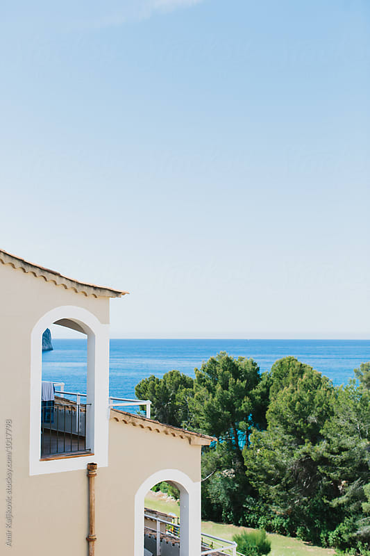 View of blue sea from balcony of resort by Amir Kaljikovic for Stocksy United