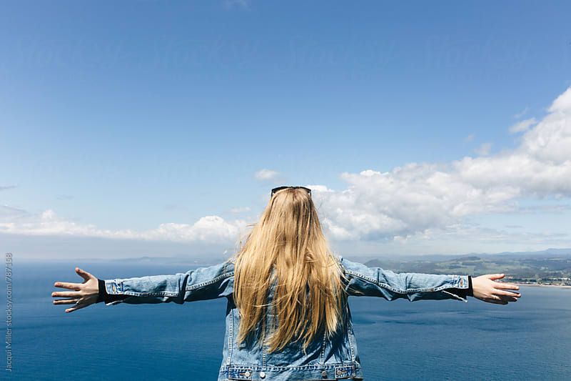 Carefree young woman looking at the ocean with her arms outstretched by Jacqui Miller for Stocksy United