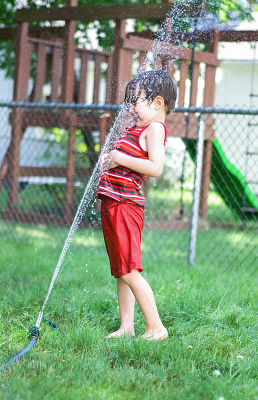 Child is sprayed in the face by his backyard sprinkler by Cara Dolan for Stocksy United